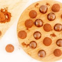 milo balls and chocolate balls on a wooden serving platter.