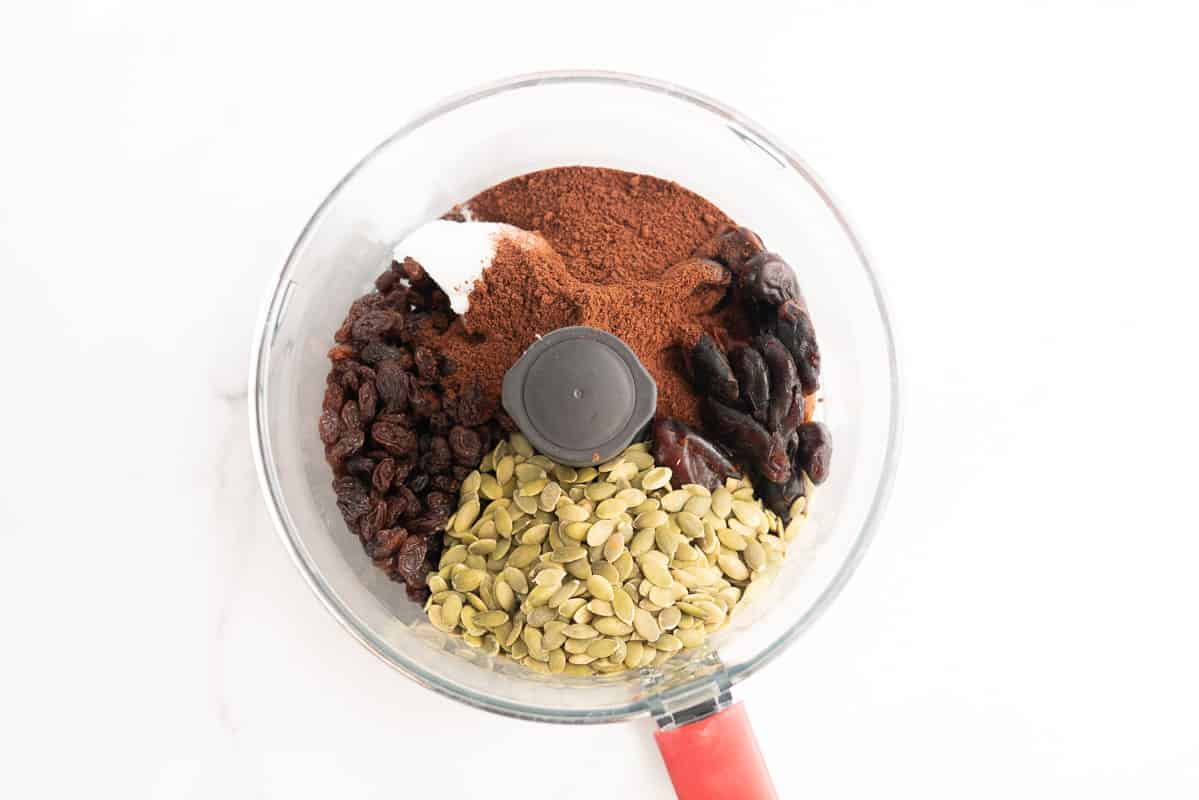 Pumpkin seeds, dates, raisins, milo, and coconut oil in a food processor.