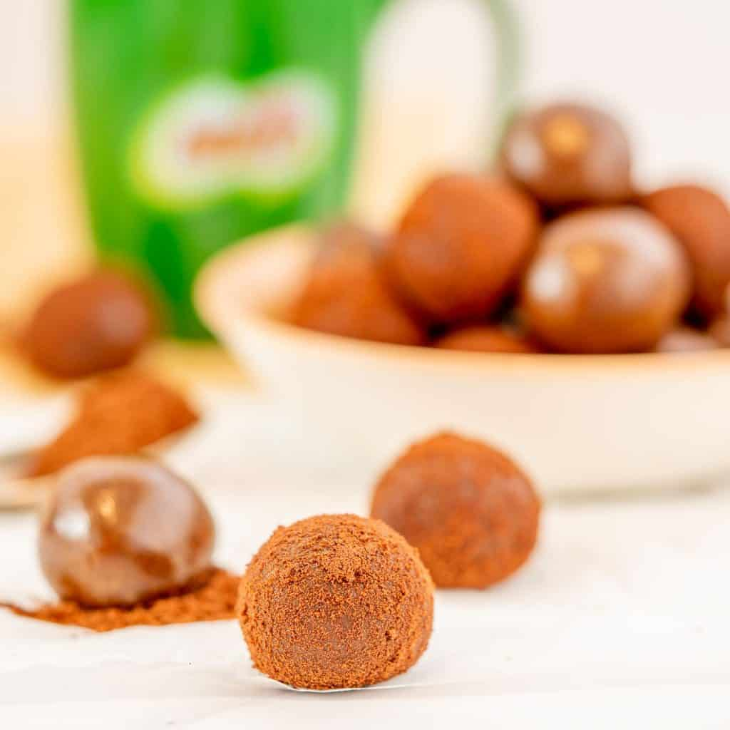 A chocolate ball rolled in milo powder sitting in front of a bowl of milo balls.
