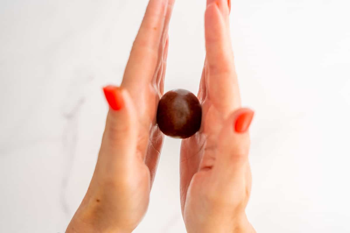 A chocolate bliss ball being rolled smooth between two hands.