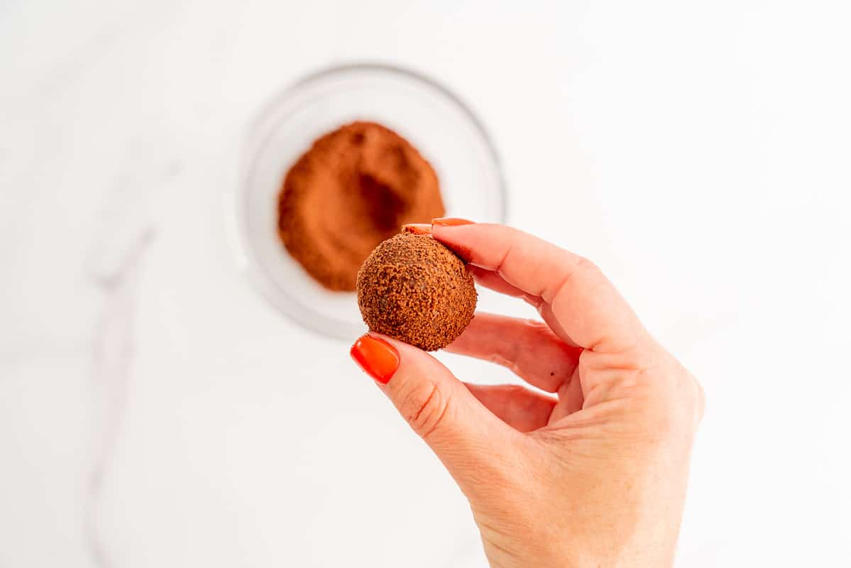 A woman's hand holding a milo coated chocolate snack ball above a small glass bowl of milo.