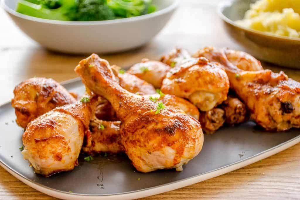 A platter of paprika chicken drumsticks in the foreground with broccoli and mashed potato in the background.