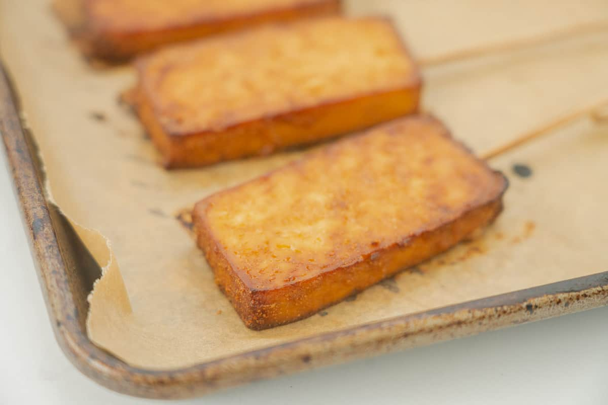 Golden brown baked tofu on a baking paper lined tray.