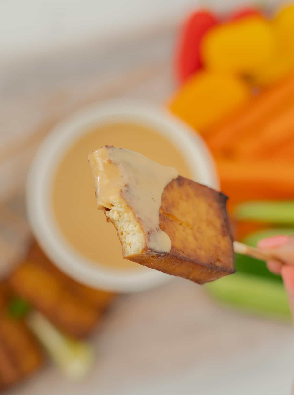 A hand holding a piece of baked tofu on a skewer, a mouthful has been eaten, revealing the creamy white centre of the tofu.