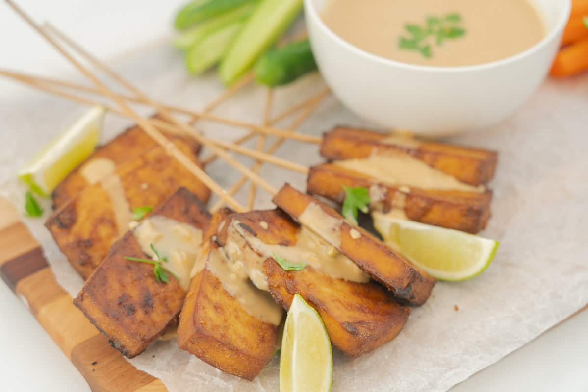 Golden brown satay tofu, drizzled with satay sauce on a serving plate.