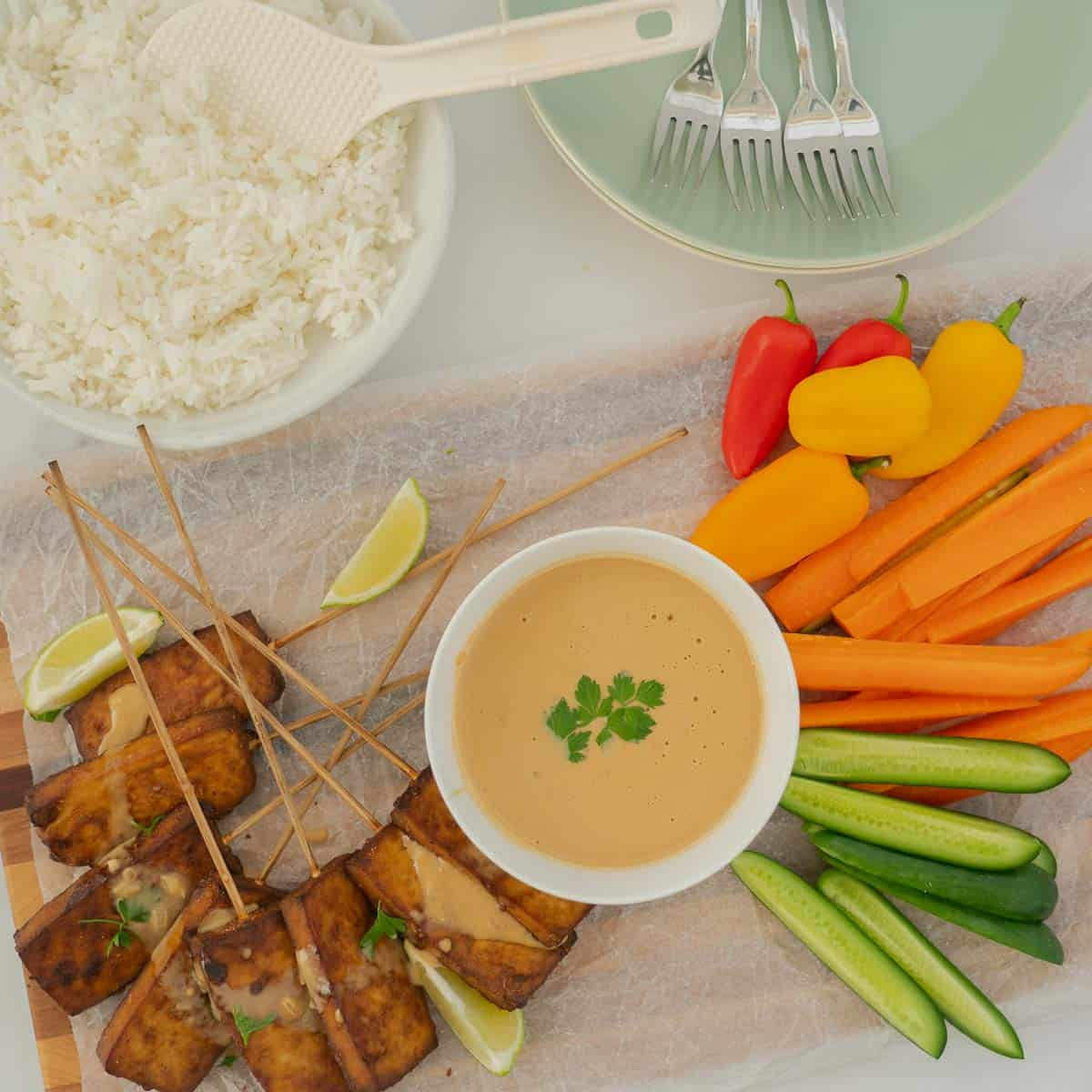 Top down photo showing baked tofu, satay sauce and vegetables laid out on a platter with a bowl of steamed rice.