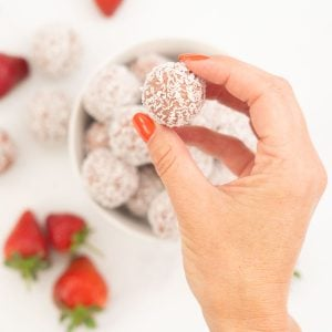 A woman's hand holding a coconut covered strawberry bliss ball.