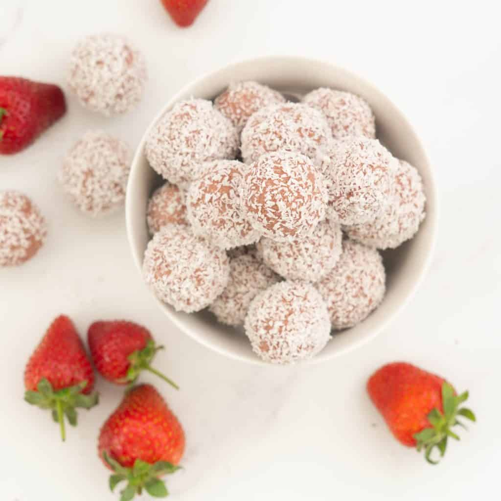 A white bowl filled with pink coconut covered bliss balls.