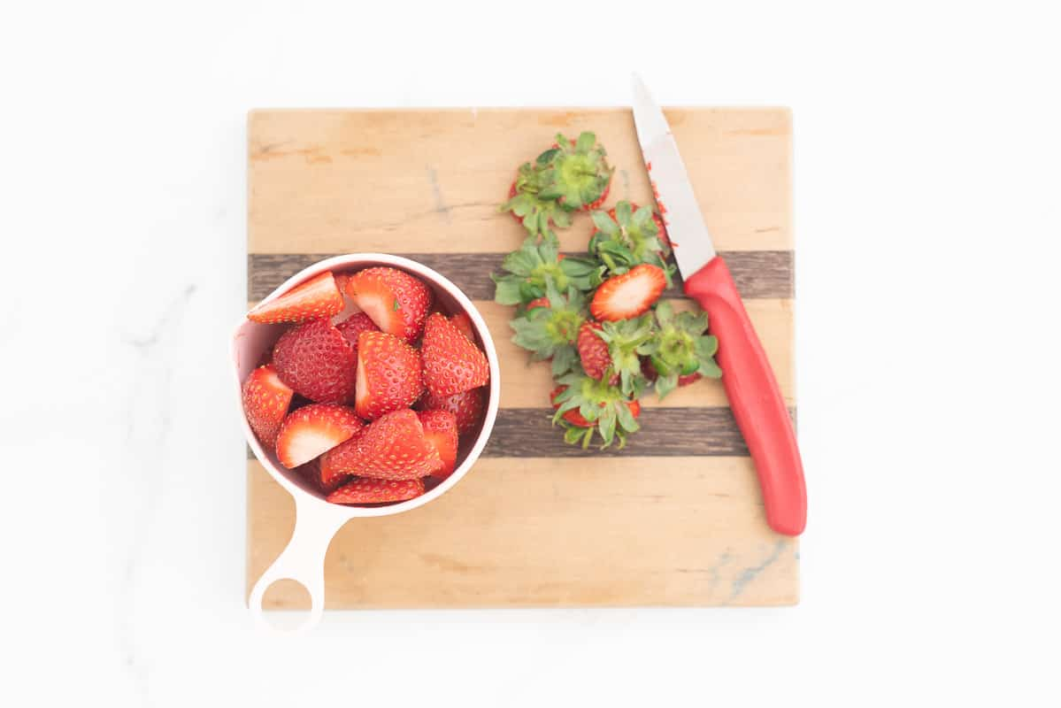 A full measuring cup of sliced strawberries nexy to a chopping board with nice and removed strawberry tops.