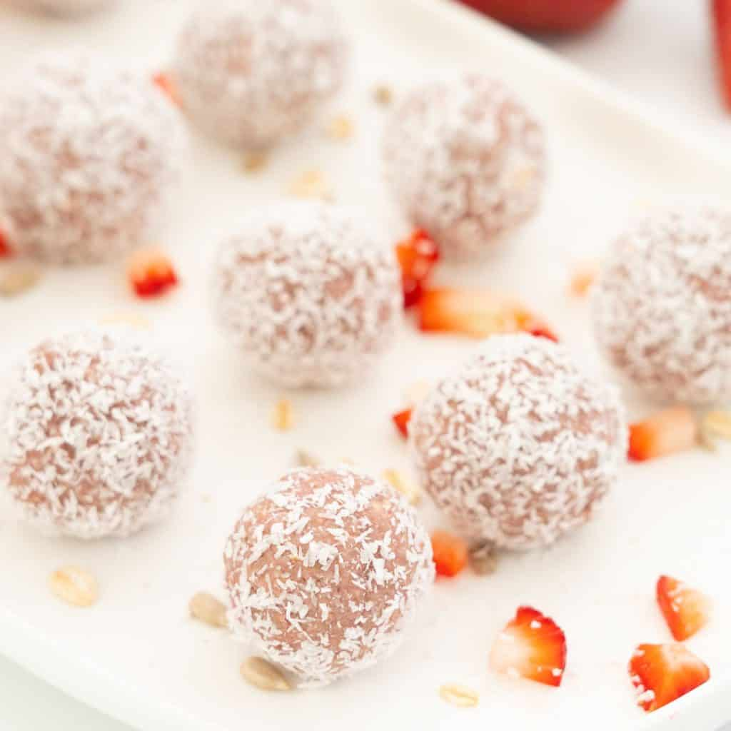strawberry balls rolled in desiccated coconut sitting evenly spaced on a white platter.