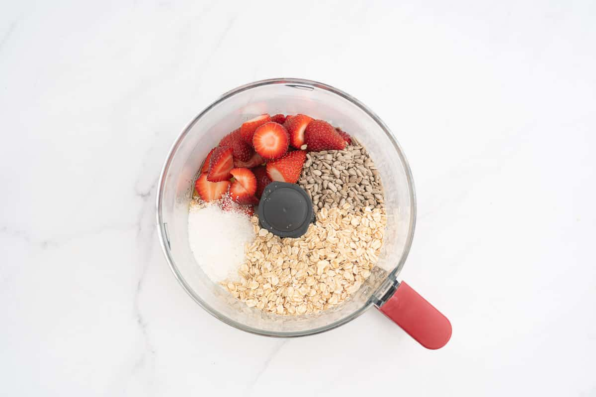 Strawberries, oats, sunflower seeds, coconut in a food processor ready to be blitzed.