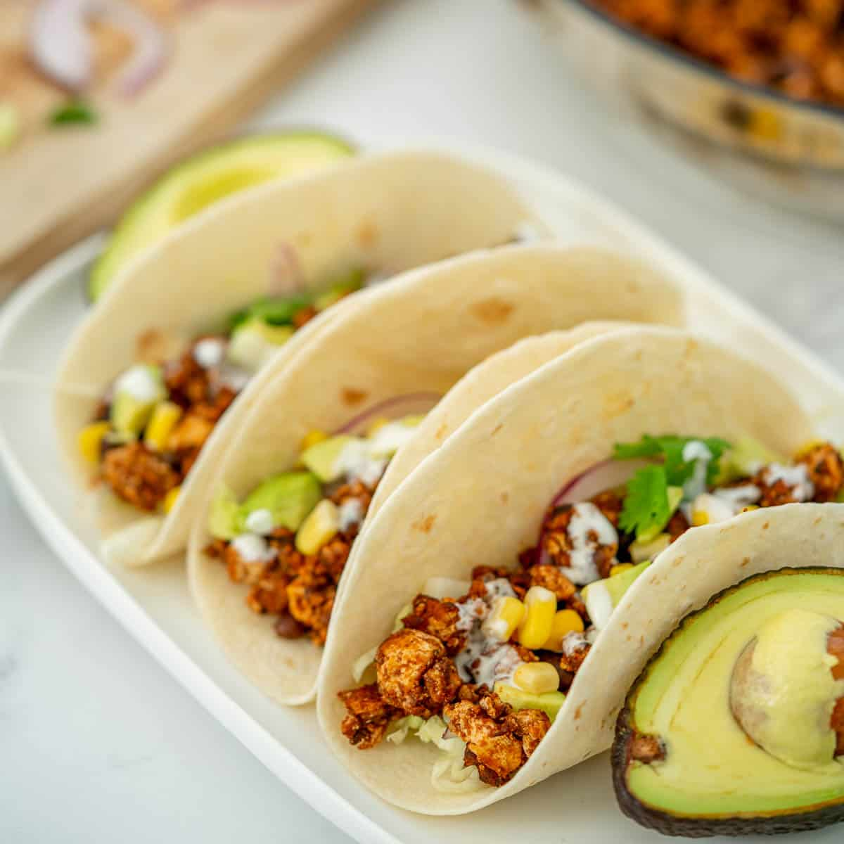 3 soft tacos filled with Mexican tofu crumbles on a white platter.