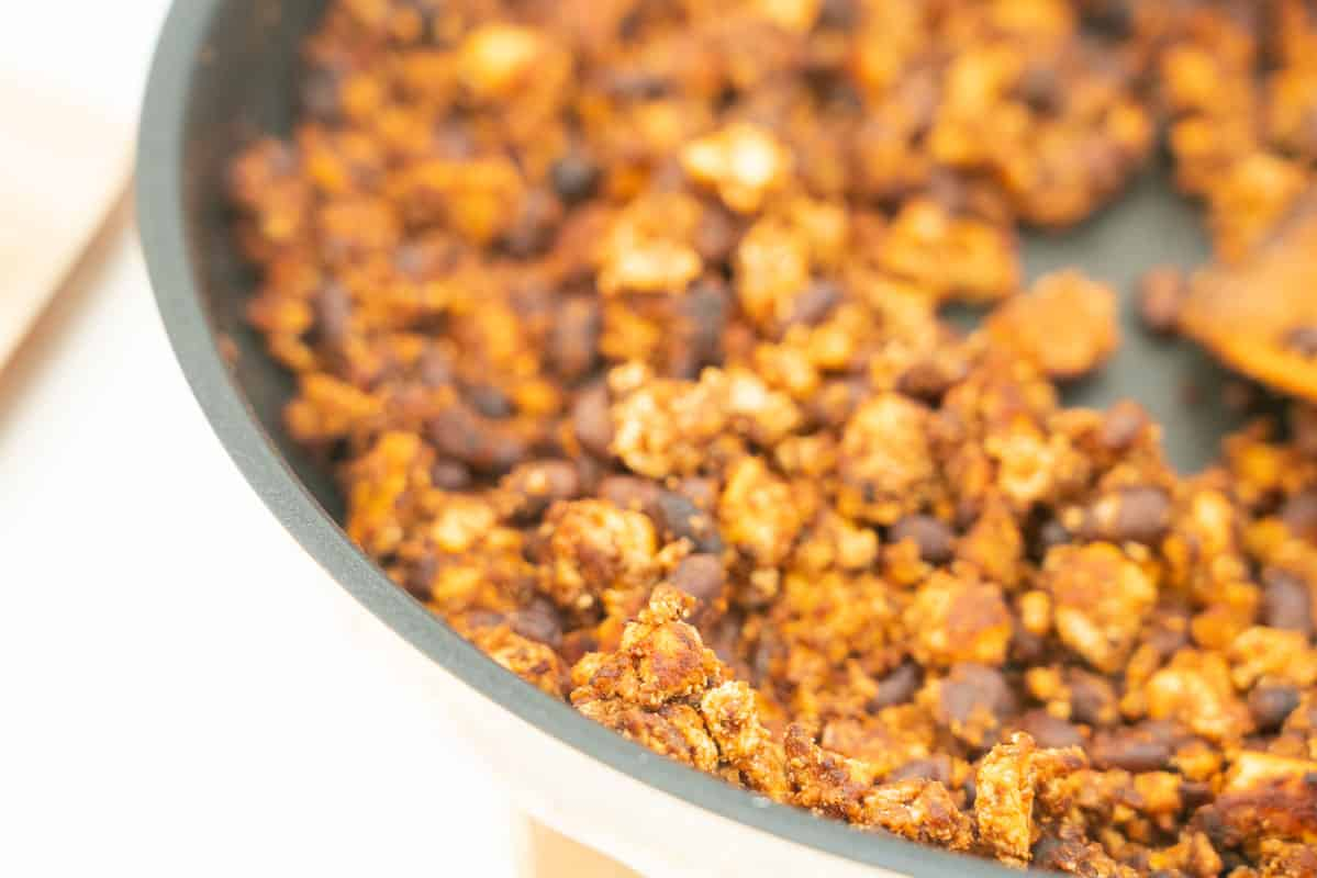 close up of cooked mexican flavoured tofu crumbles in a skillet, black beans also visible.