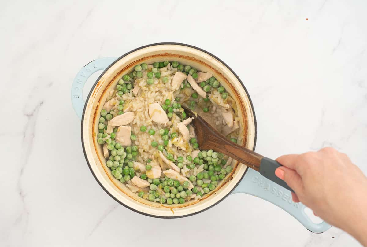 Frozen peas being stirred through a risotto with a wooden sppon.