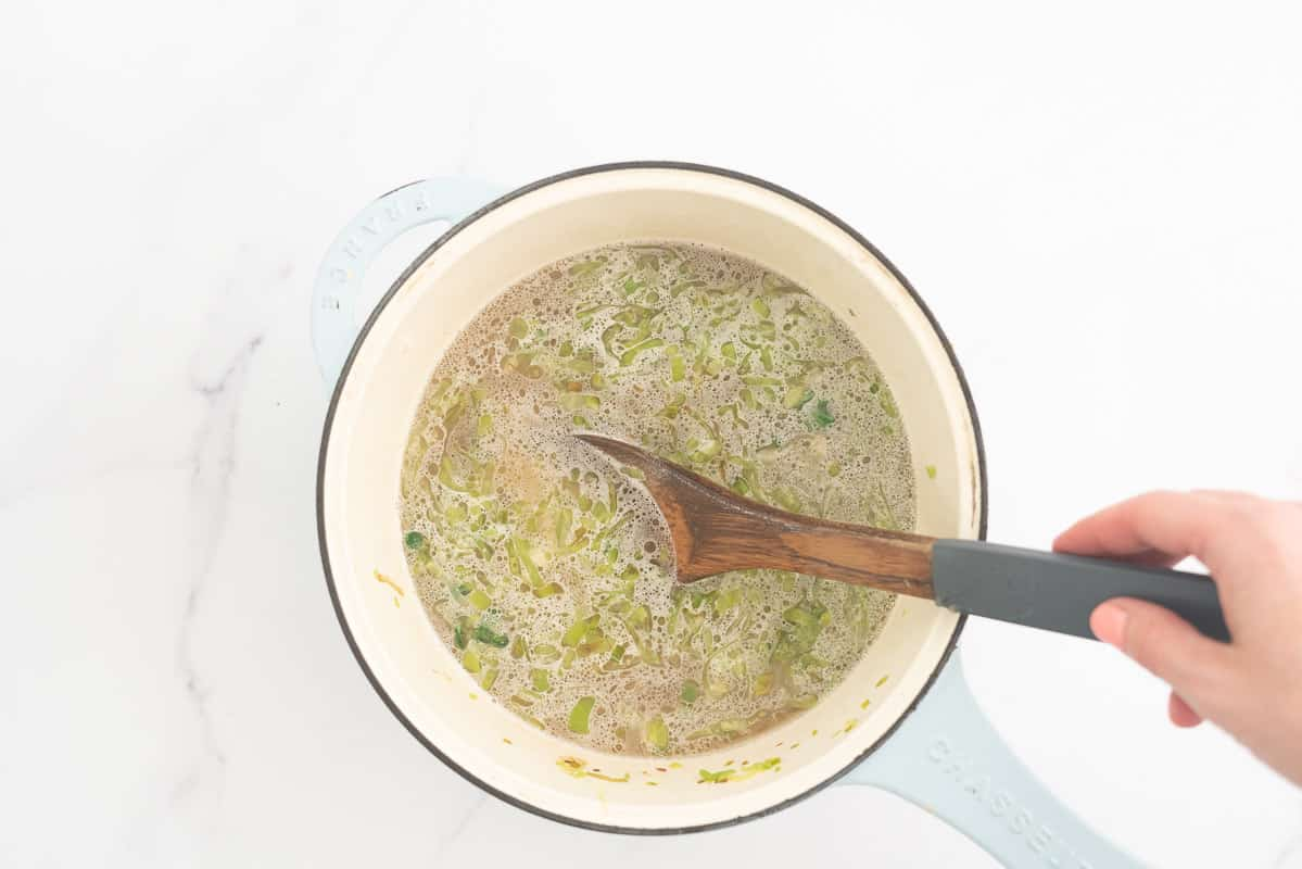 A large ceramic pot filled with stock, sliced leek and arborio rice.