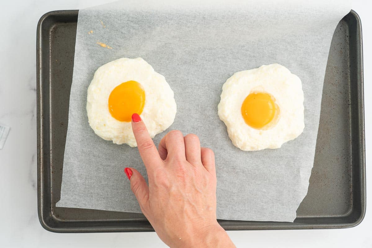 Woman's hand pointing to an egg yolk in the centre of a baked cloud shaped meringue.