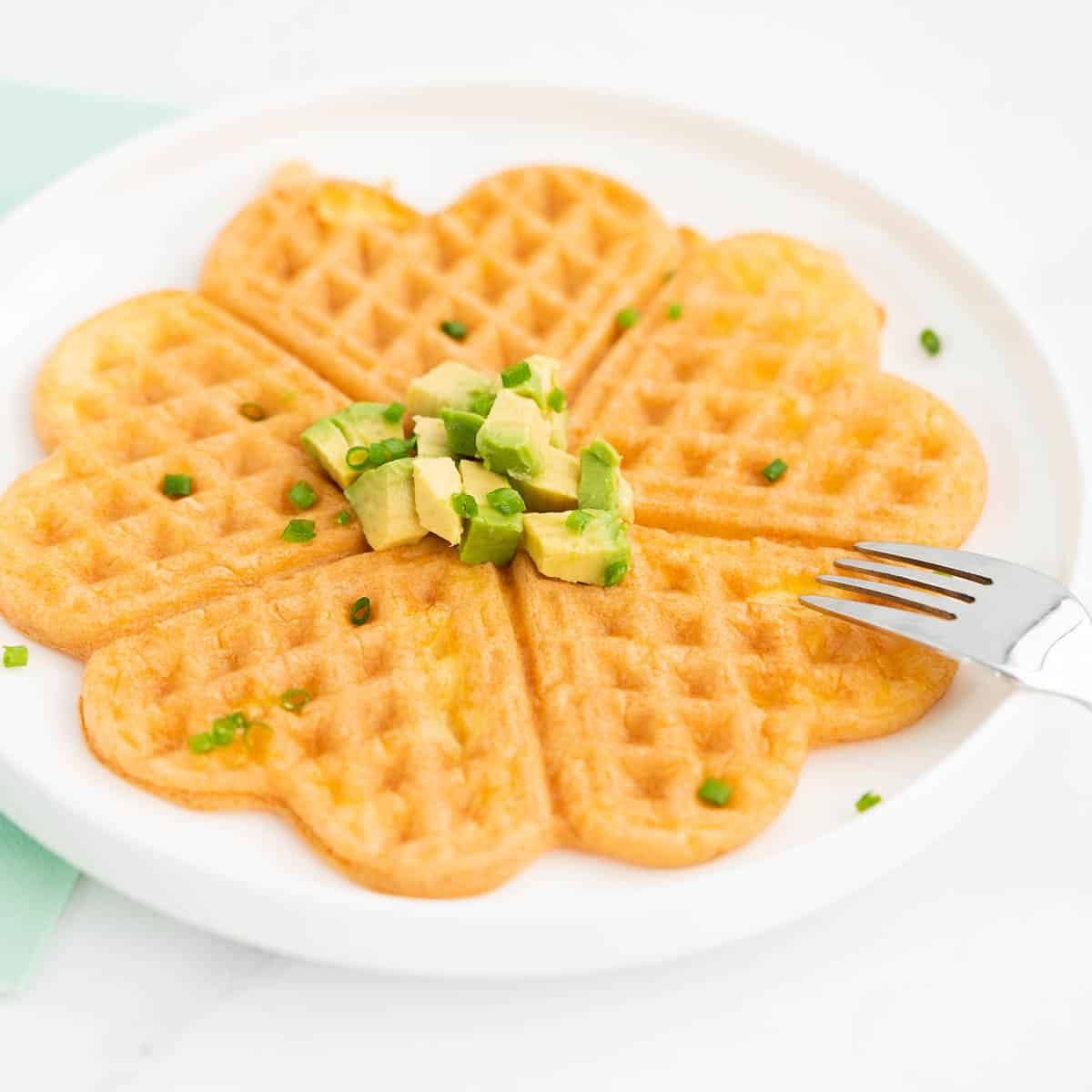 An egg waffle on a white plate garnished with small cubes of avocado and chives.