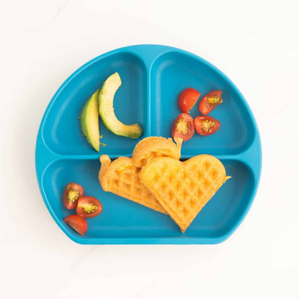 a blue silicone divided plate with 2 heart shaped egg waffles, sliced tomatoes and avocado.