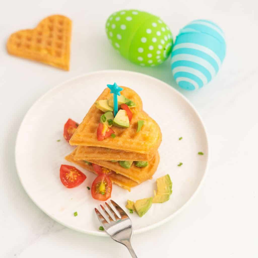 heart shapped waffles stacked up on a white plate with easter eggs in the background.