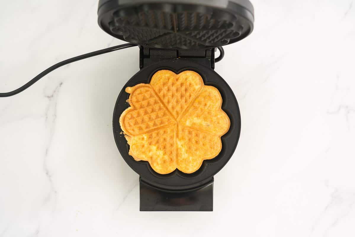 A golden cooked egg waffle sitting in an open waffle maker.