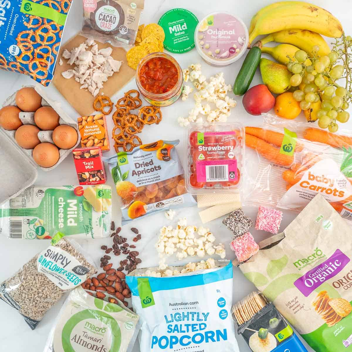 A collection of lunch box snacks you can grab at a supermarket laid out on a bench.