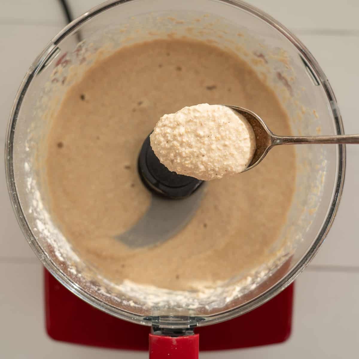 A spoonful of oat pancake batter being held above a food processor.