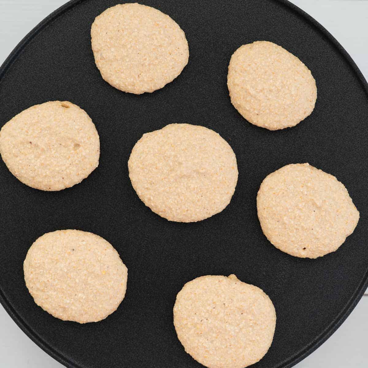 Pancakes cooking on a pancake pan.