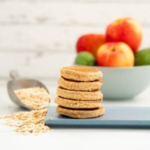 A stack of five pancakes on a blue platter, a bowl of apples and rolled oats in the background.