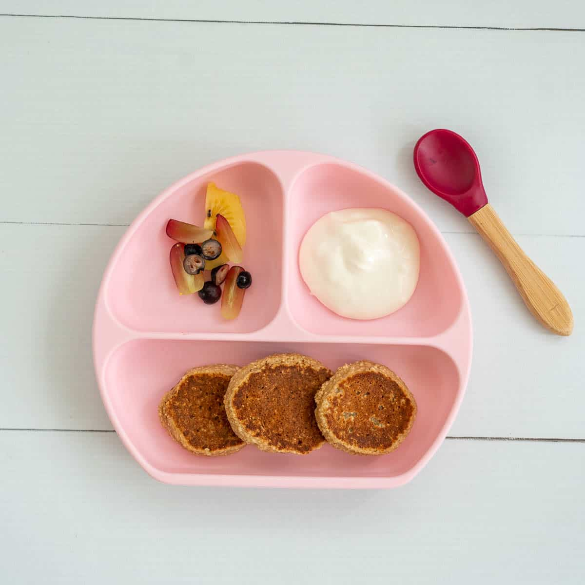 A pink divided baby plate, with 3 baby pancakes, sliced fruit and yoghurt.