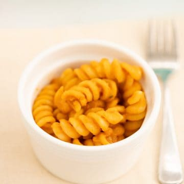 Sauce covered pasta spirals in a small white ceramic bowl.