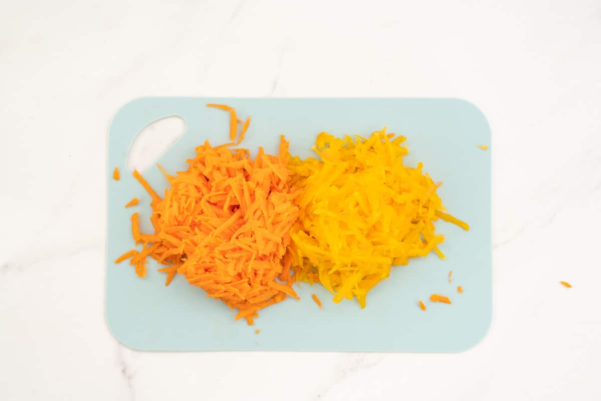 Piles of grated carrot and grated pumpkin on a blue chopping board.