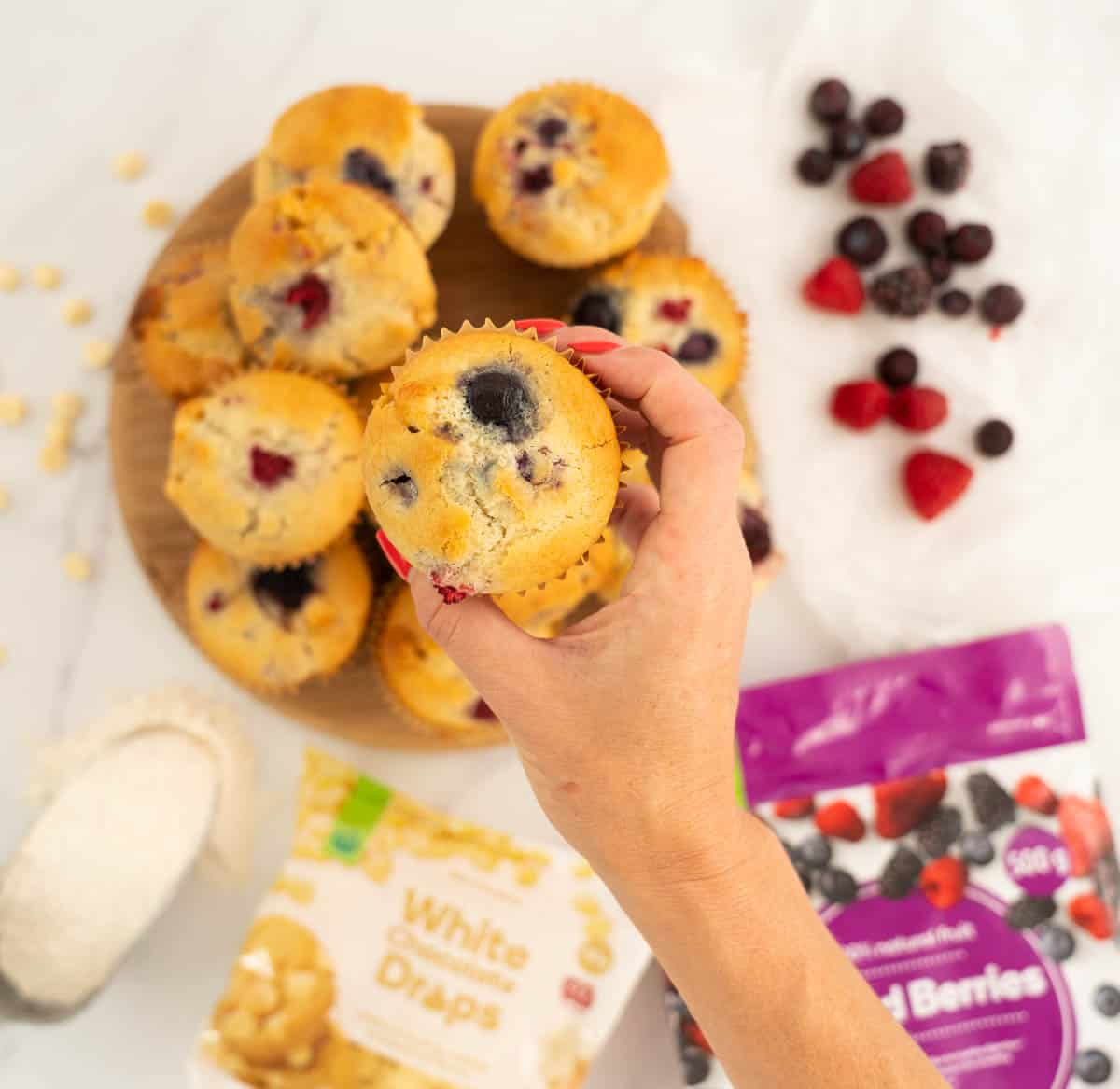 Woman's hand holding a berry muffin above a wooden tray of muffins.
