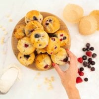 Women's hand reaching for a berry muffin from a wooden tray of a dozen muffins.