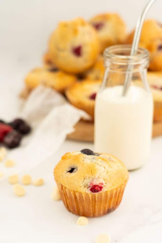 A berry muffin sitting next to a glass of milk with a straw.