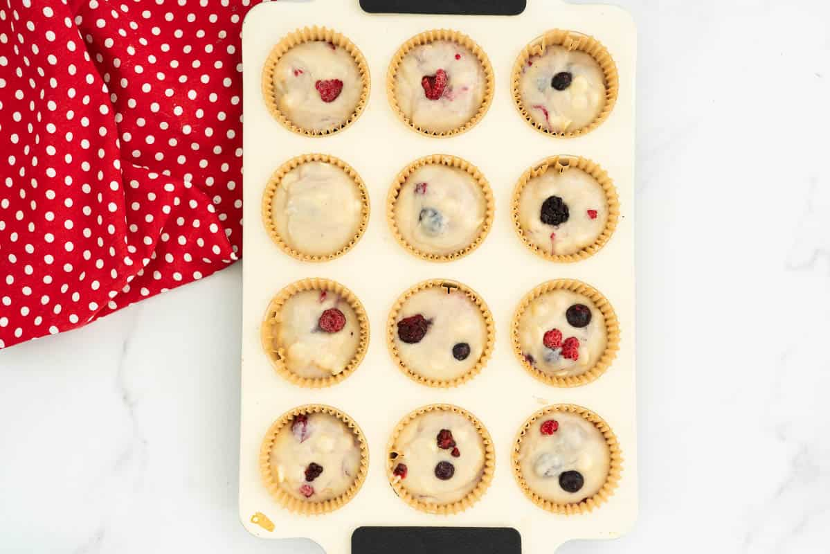 berry muffin batter portioned into a 12 cup muffin tray.