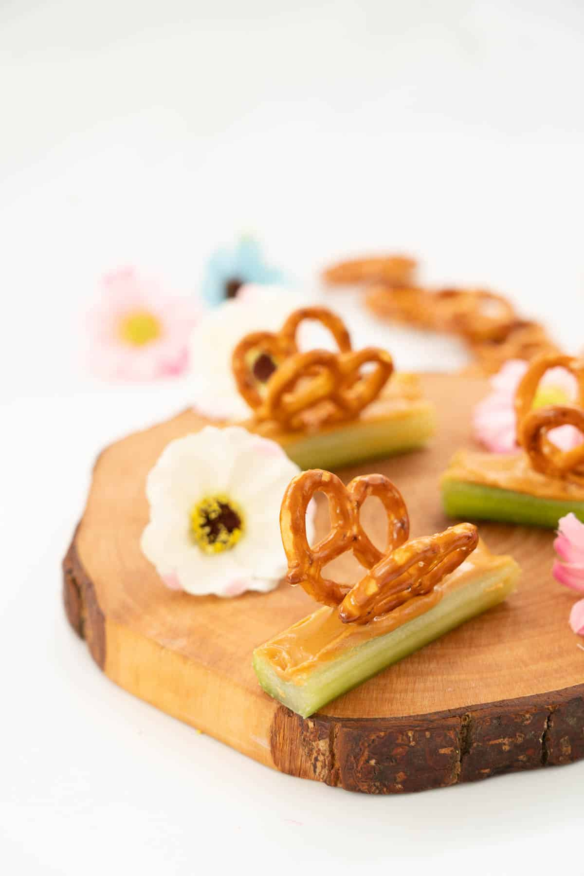 Celery sticks filled with peanut butter decorated with pretzels to form wings, making a butterfly snack., on a wooden board scattered with small flowers.