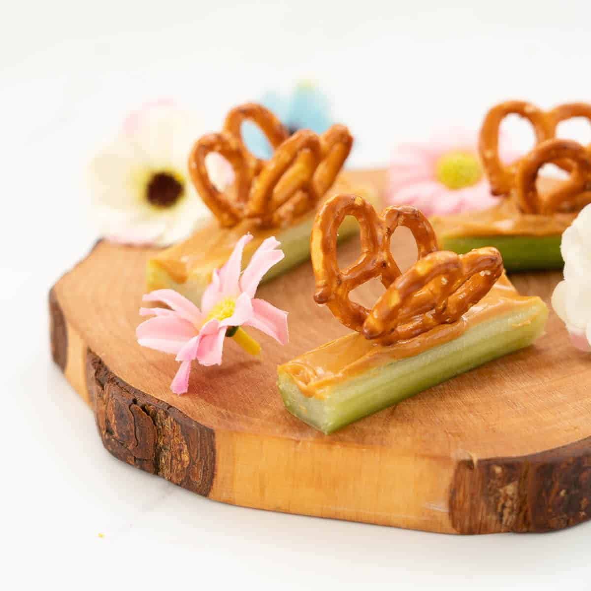 Celery sticks filled with peanut butter decorated with pretzels to form wings, making a butterfly snack.