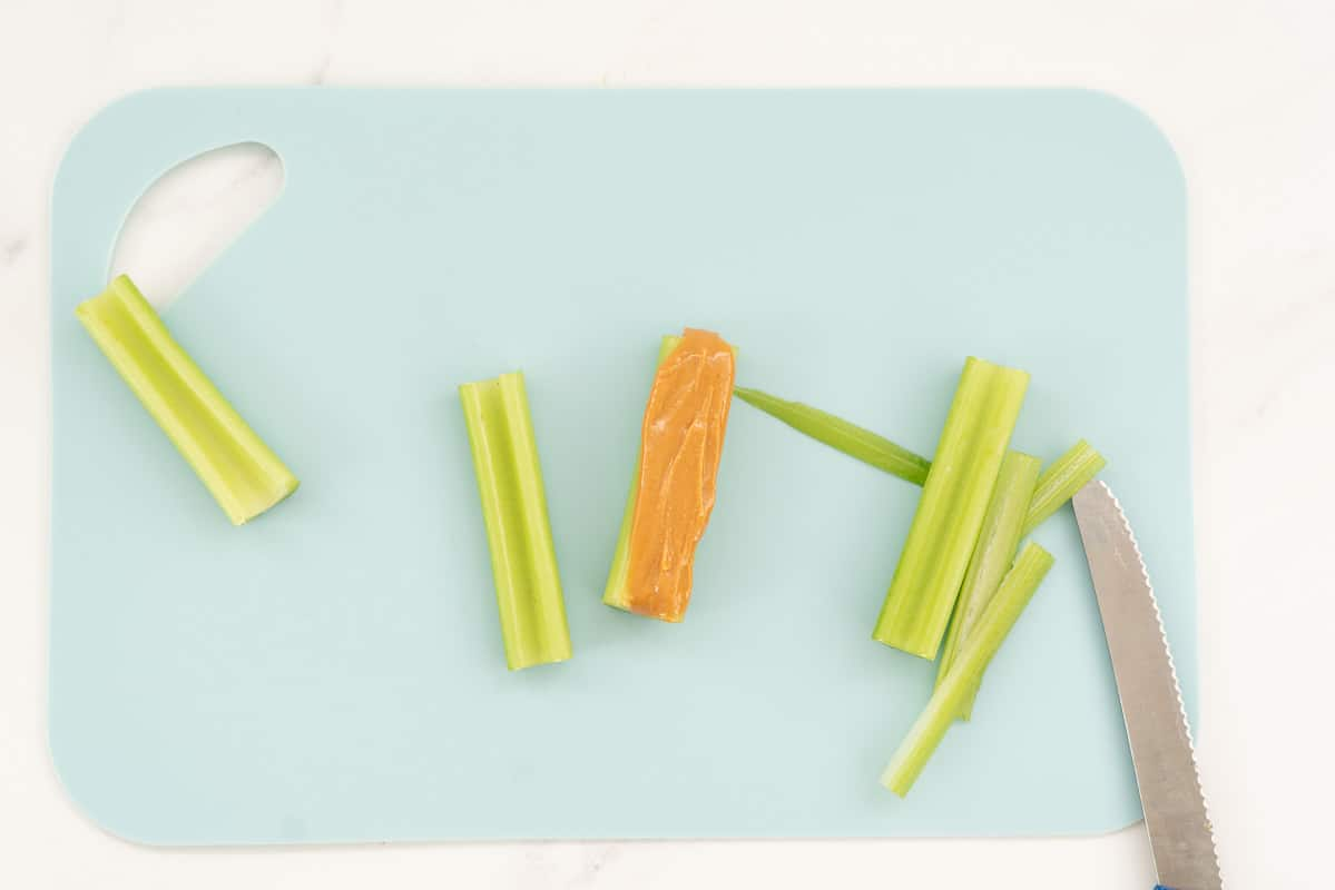 Celery sticks on a blue chopping board, one filled with peanut butter