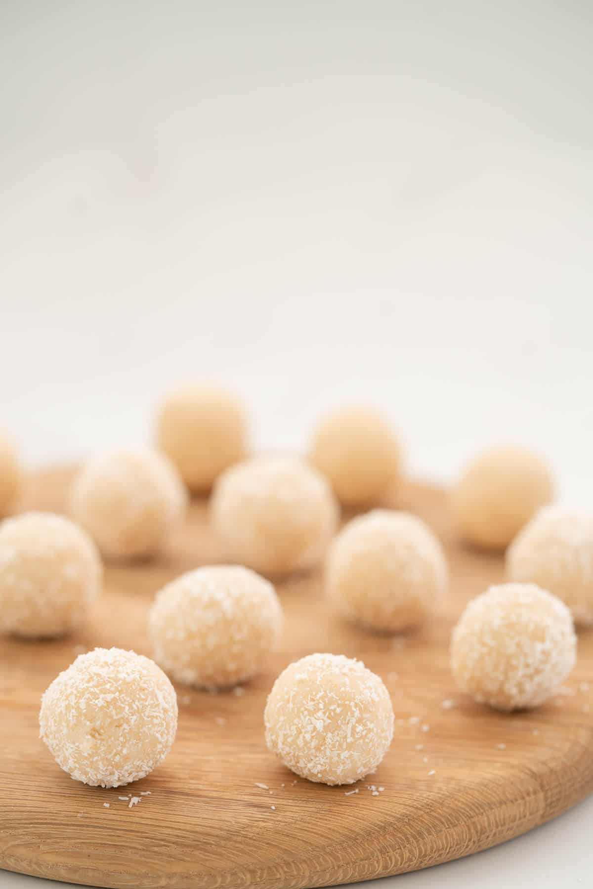 White coconut balls served on a round woodden board.
