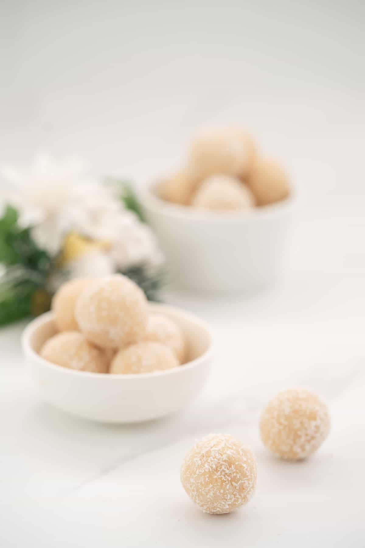 Coconut balls on a white marble bench top with christmas decorations in the background.