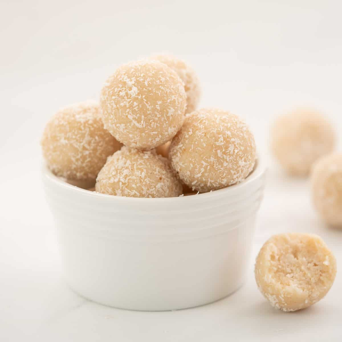 A small white bowl of coconut balls.