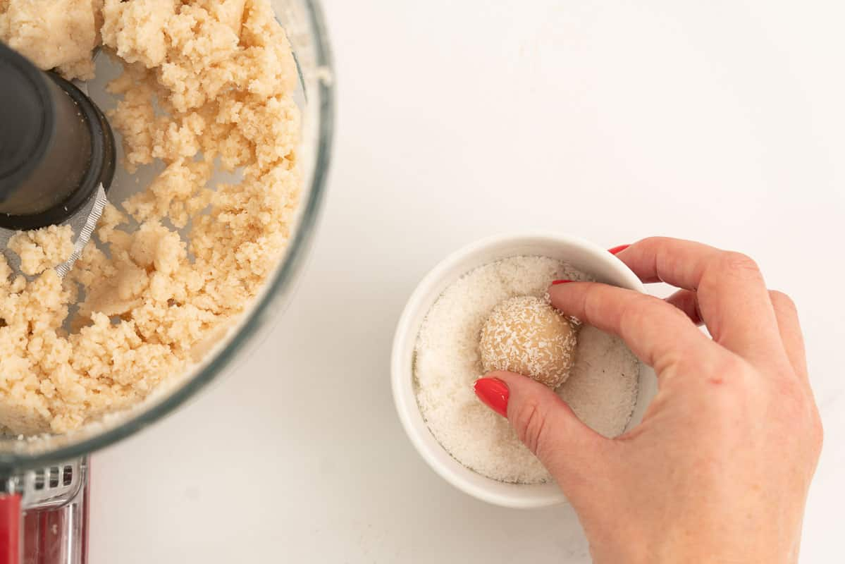 A coconut bliss ball being rolled in a small bowl of desiccated coconut.