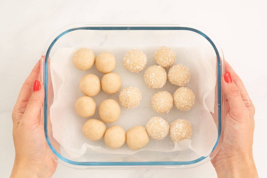 Coconut snow balls in a baking paper lined glass container ready to go into the fridge.