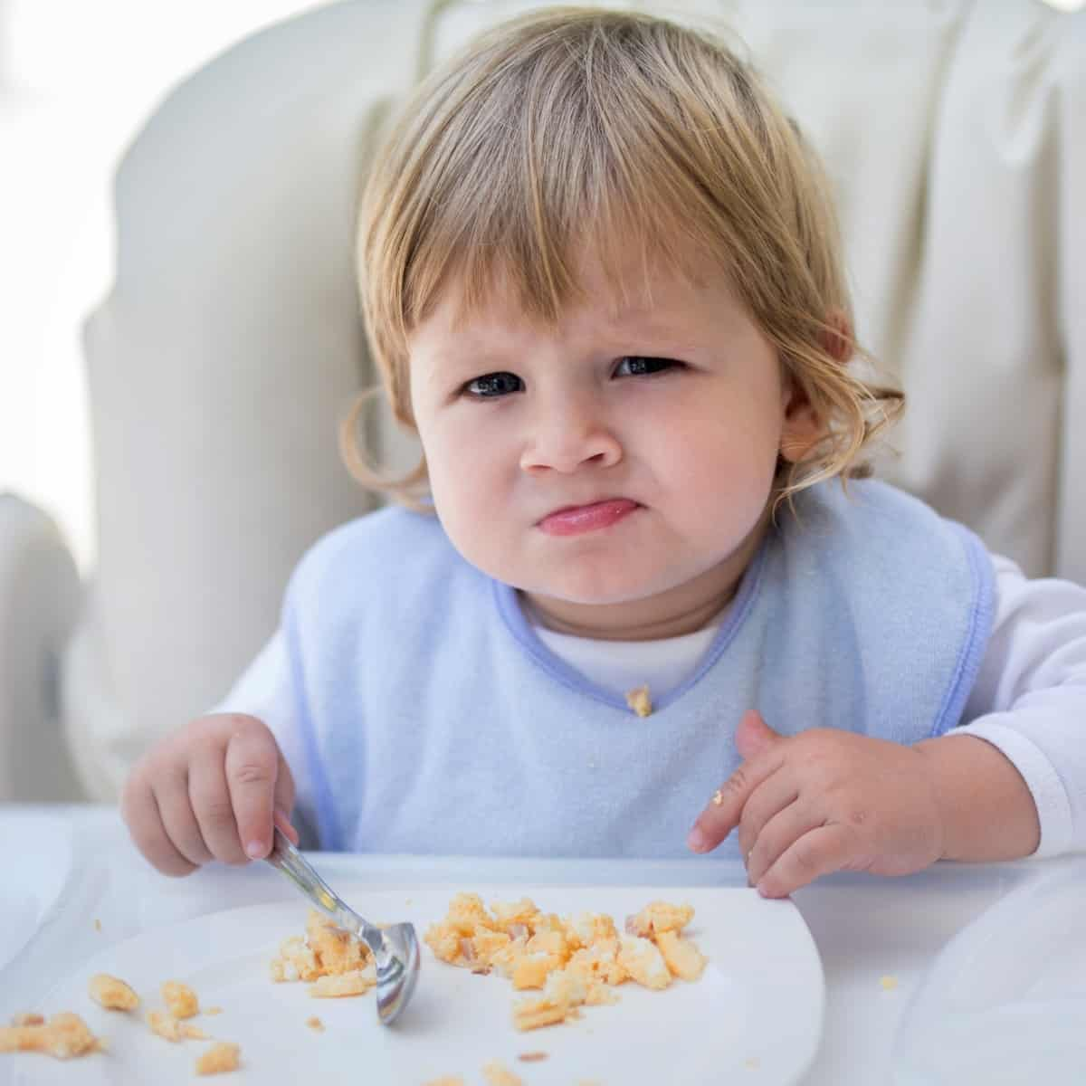 A toddler sitting in a high chair with a plate of scrambled eggs.