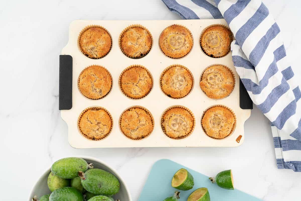 12 golden brown feijoa muffins in a cream muffin tin.