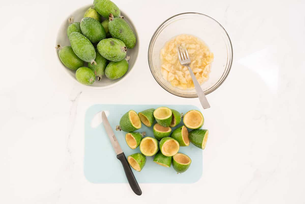 Feijoa skins on a blue chopping bowl, feijoa flesh in a glass bowl with a fork.