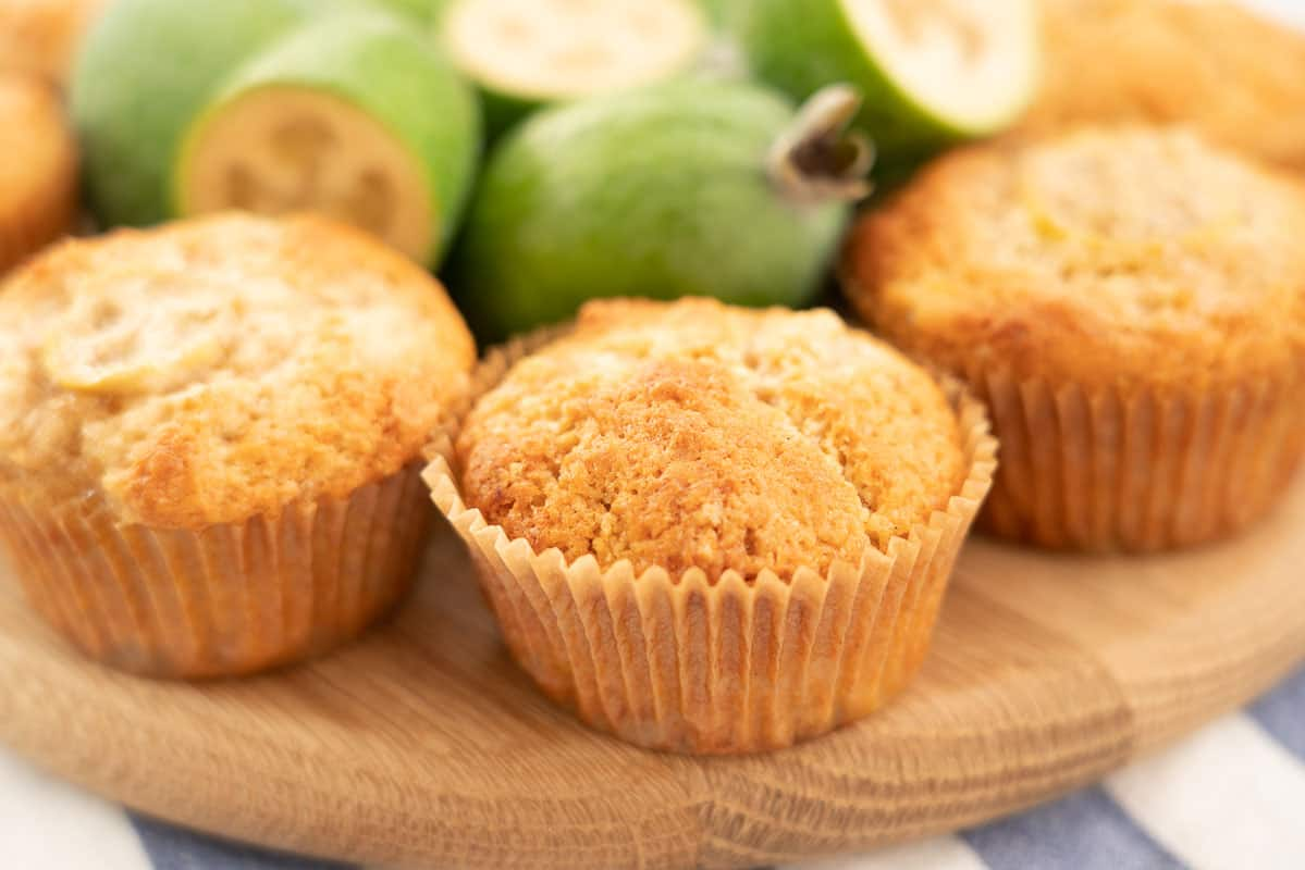 Golden muffins sitting on a wooden board with fresh feijoas.