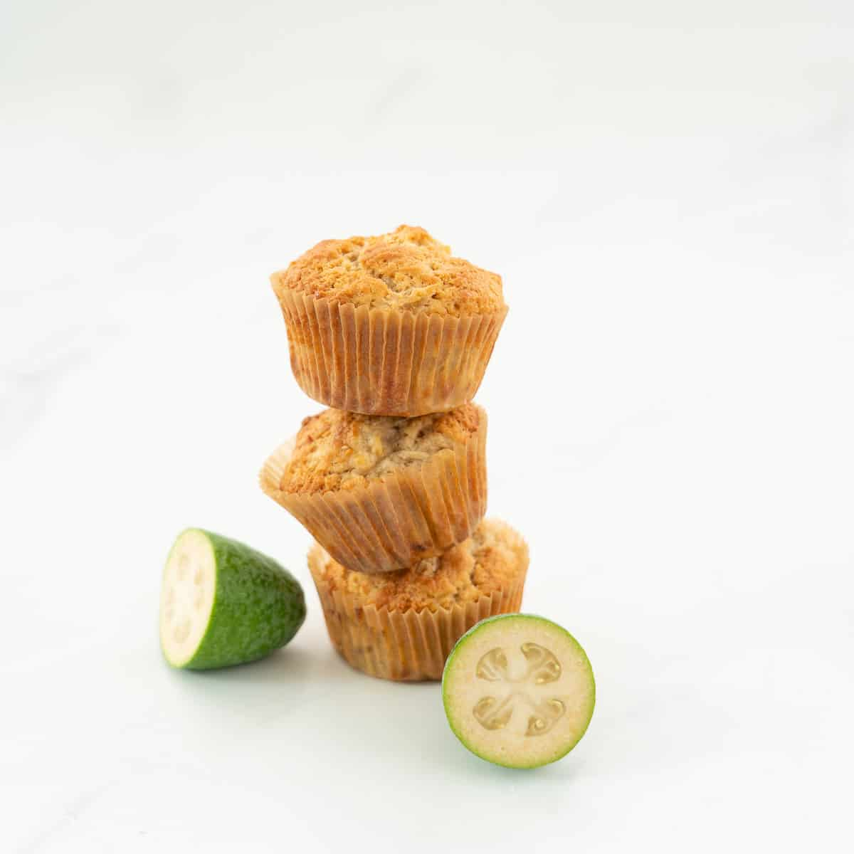 Stack of 3 muffins with a halved feijoa.