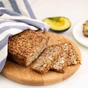 Seeded oat bread sliced on a wooden chopping board.