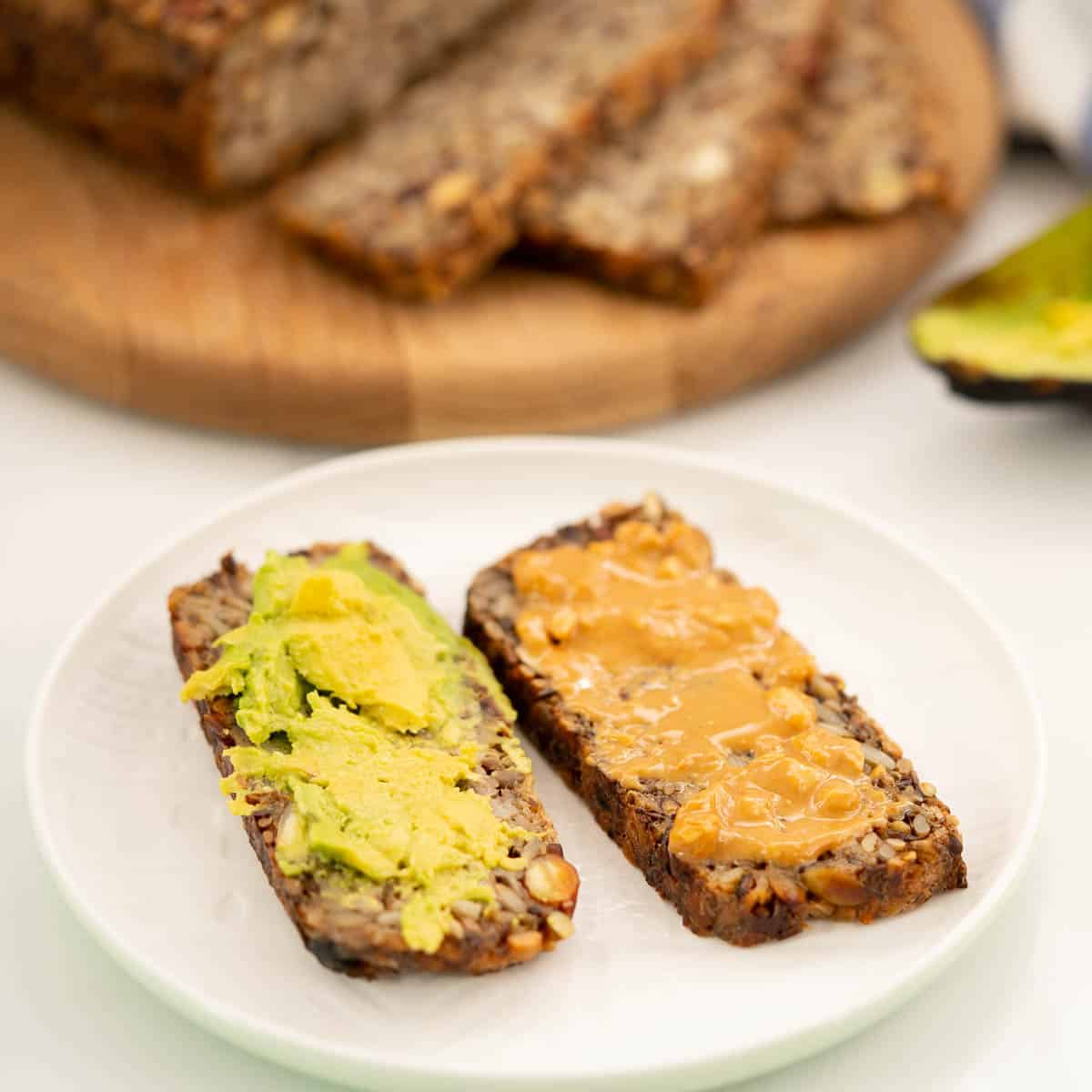 2 slices of oat toast spread with avocado and peanut butter.